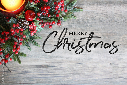 Fotografie, Obraz  Merry Christmas Text, Festive Holiday Candle, Pine Tree Branches and Berries in