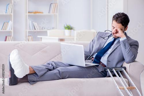 Fotografia, Obraz Businessman with crutches and broken leg at home working