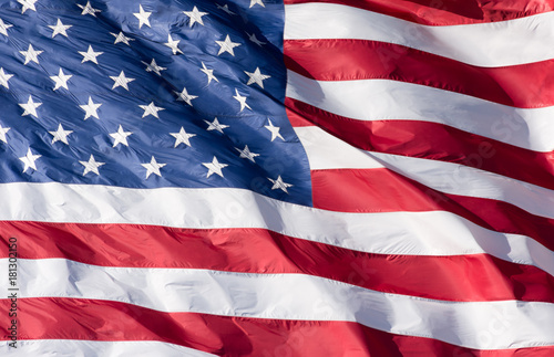 Close up the stars and stripes of the American flag that is waving in the wind.