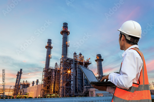 Fototapeta  Engineering is use notebook check and  standing in front of oil refinery building structure in heavy petrochemical industry obraz