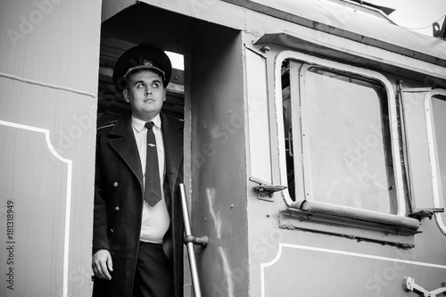 European or American train conductor is on his duty on a platform and other trains Canvas Print