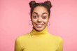 Happy excited surprised female model with two hair buns, raises eyebrows as being amazed with something, can`t believe in her success, glad to be praised, poses against pink studio background