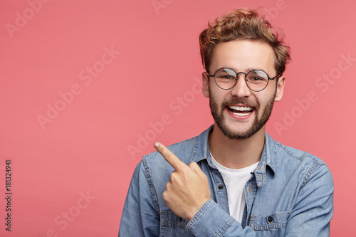 Fotografía  Stylish unshaven man in denim shirt points at copy space on pink wall as shows something pleasant, has smiling look, advertises product
