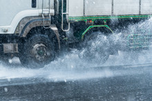 Rainwater Spraying From Motion Truck Wheels. City Road During Heavy Rain.Thailand.