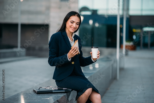 Happy business woman with sandwich and coffee Wallpaper Mural