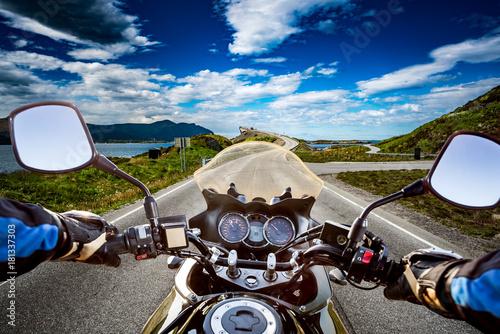 Fotografia  Biker rides a road with Atlantic Ocean Road in Norway