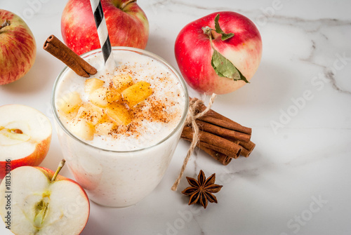 Fototapeta Healthy vegan food. Dietary breakfast or snack. Apple pie smoothies, with apples, yogurt, cinnamon, spices, walnuts. In a glass, on a white marble table. Copy space obraz