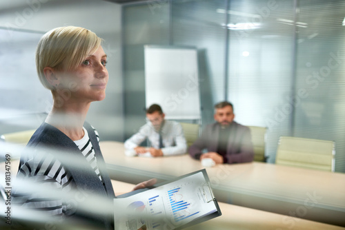 Fototapeta Portrait of ambitious young woman standing in office looking away hopefully and smiling with three people at meeting table in background, copy space obraz na płótnie