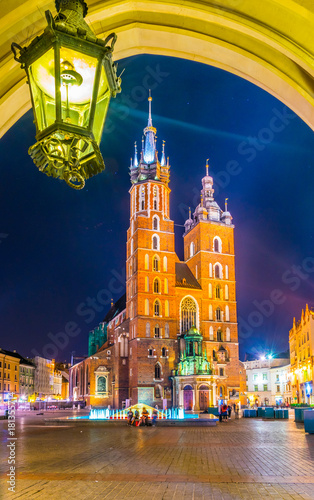Fototapeta Night view of the church of Saint Mary in the polish city Cracow/Krakow viewed from an arch of the Sukiennice marketplace (Cloth Hall, Drapers' Hall) obraz