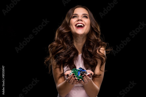 Fotografie, Obraz  Female Poker player with paint black nails hold her poker chips to make a bet