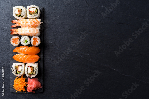 Poster de jardin Sushi bar Overhead shot of Japanese sushi on black concrete background
