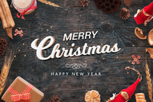 Merry Christmas And Happy New Year Text On Black Wooden Desk With Christmas Decorations. Top View.