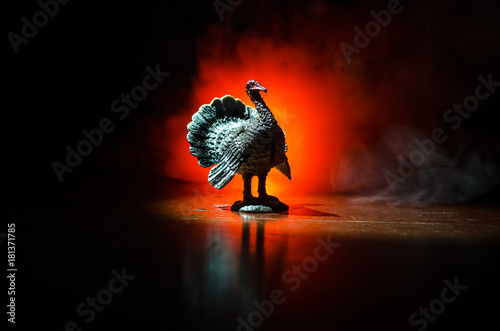 Photo  Statue of Turkey Tom strutting his stuff with red wattles and blue/white head on a smoke toned dark background