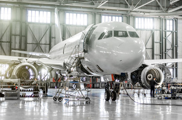 Passenger aircraft on maintenance of engine and fuselage repair in airport hangar.
