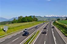 A3 - Autobahn Mehrspurig Zwischen Zürich Und Chur. Autos Beim Fahren, Im Hintergrund Schweizer Schneeberge,