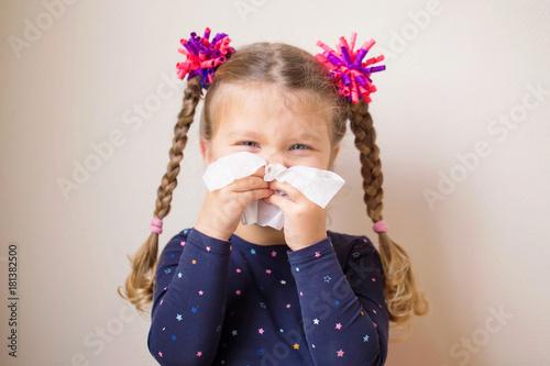 Fényképezés  The little girl with runny nose blows into handkerchief.
