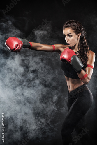 Photo  A strong athletic, woman boxer, boxing at training on the black background