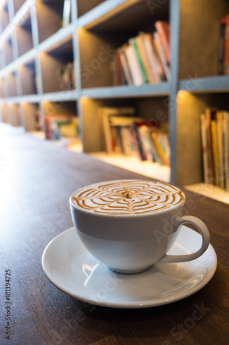 Cup Of Coffee Latte Art On Wooden Table With Bookshelf Background