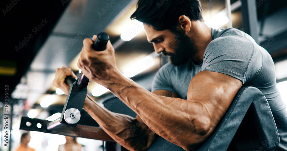 Fototapeta Young handsome man doing exercises in gym