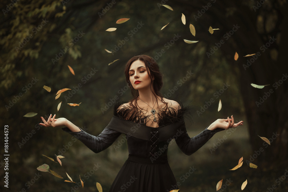 Fototapeta Incredible, amazing, seductive girl, in a black dress , magic rotates the leaves. The background is fantastic autumn. Artistic photography.