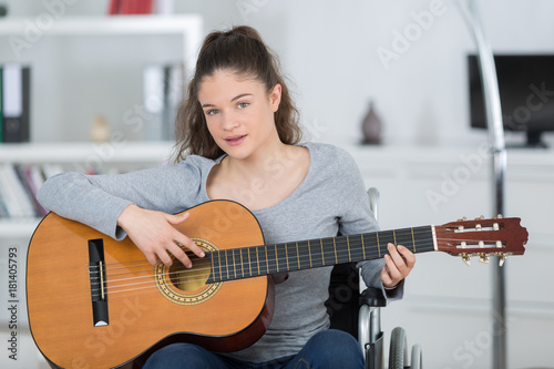 Valokuva  disabled girl playing guitar in her living room