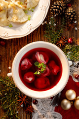 Fototapeta Christmas beetroot soup, borsch with small dumplings with mushroom stuffing in a ceramic bowl, top view. Traditional Christmas eve dish in Poland.