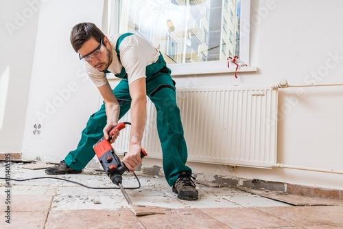 Photo Demolition of old tiles with jackhammer. Renovation of old floor.