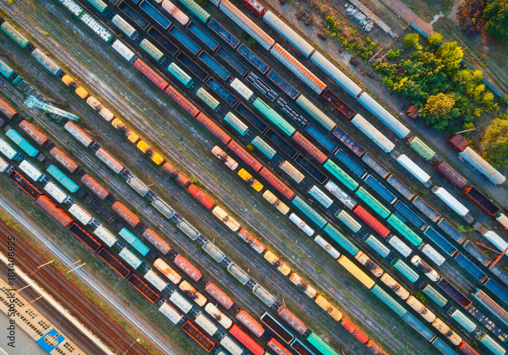 Fototapety, obrazy: Top view of colorful cargo trains. Aerial view from flying drone of colorful freight trains on the railway station. Wagons with goods on railroad. Heavy industry. Industrial conceptual scene