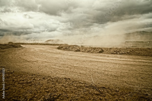 Obraz na płótnie carretera de tierra con polvo por el viento un dia nublado