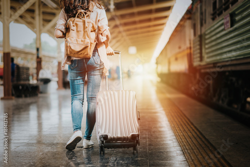 Woman traveler tourist walking with luggage at train station Canvas