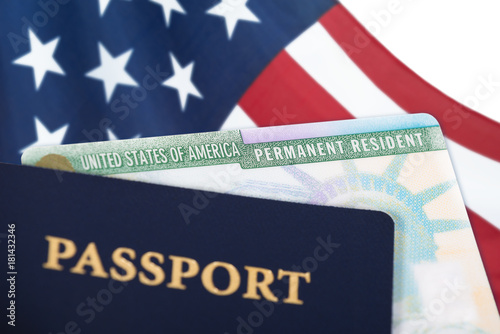 Valokuvatapetti United States of America permanent resident card, green card, displayed with a US flag in the background and a passport in the foreground