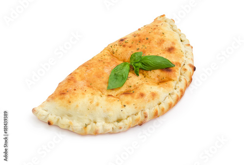 Cooked calzone with basil twig on a white background