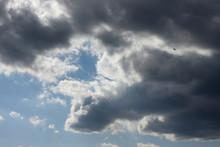 天空を飛ぶ飛行機と青空と雲(灰色に見える雲と白い雲=闇と光の対比イメージ)・明暗を分ける、心の隙間、困難を乗り越えるなどのイメージなど・雲などに文字入れスペース