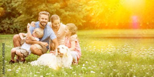 фотография  Glückliche Familie mit Kinder und Hund im Garten