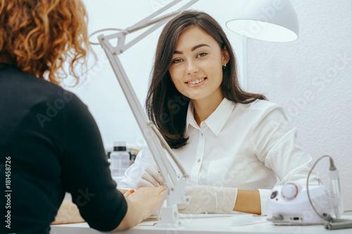 Photo  Manicurist does manicure for client