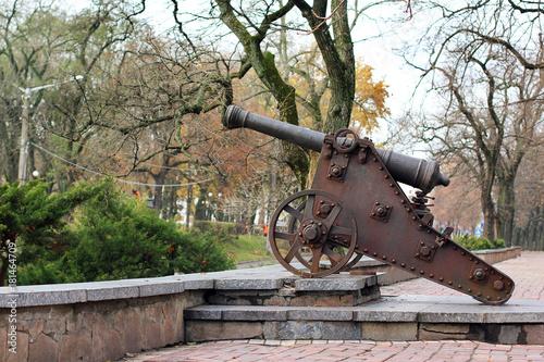 Plakat Czarna stara armata na wzgórzu. Pistolet wojskowy. Stara armata na tle miasta. Ochrona miasta. Wojna. Ochrona. Broń. Armia