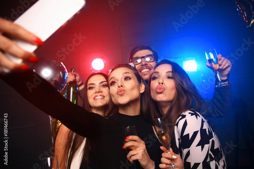 Fotografía party, technology, nightlife and people concept - smiling friends with smartphone taking selfie in club