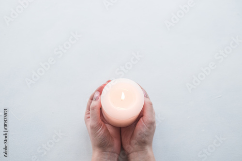 Hand holding candle as a sign of remembrance or mourning on white background Fototapete
