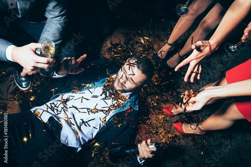 Fotografie, Obraz  Crazy party. Drunk man lying on floor