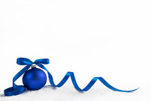 Christmas Ball With Blue Ribbon On Artificial Snow Flakes.