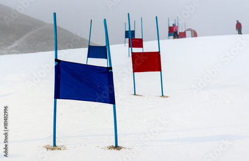Fotomural  Children skiing slalom racing track with blue and red gates.