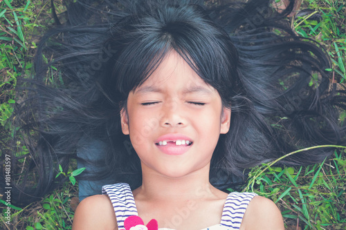 Photo  Toothless Little girl closing her eyes  sleeping on the grass in the park