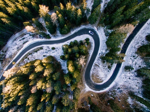 Poster de jardin Vue aerienne Aerial view of snowy forest with a road. Captured from above with a drone