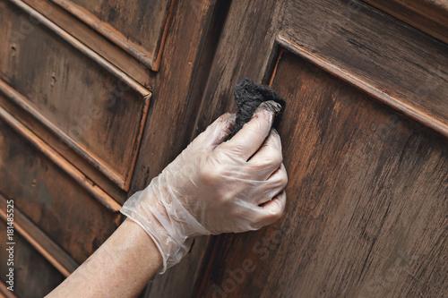 Photo femme patinant meuble en bois ancien à la cire