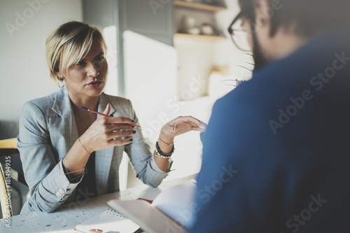 Coworkers working process at home.Young blonde woman working together with bearded colleague man at modern home office.People making conversation together.Blurred background.Horizontal.