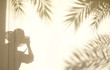 Conception for exotic travel. The shadow of the leaves of a palm tree and a photographer in a hat on a light wall at sunset or sunrise. Template background for text, wallpaper.