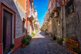 Fototapeta Na drzwi - View of narrow street typical of Italian villages - View of beautiful Carloforte (Sardinia, Italy) narrow street.