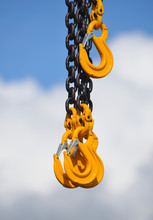 Heavy Duty Chain And Yellow Hooks Against Cloud And Sky
