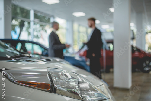 Obraz Auto showroom, dealer talking with buyer. Electro cars in moderm vehicle salon. - fototapety do salonu