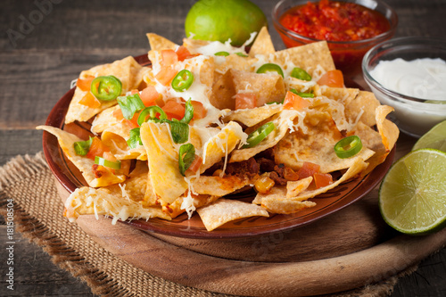 Fotomural Corn Mexican nachos with beef, jalapeno, cheese, pepper, olives and chili con carne on a wooden background